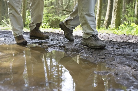 vacationer: Low section of hikers walking through a mud puddle in forest Stock Photo