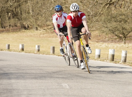 sportsperson: Active male bike riders riding cycles on a country road Stock Photo