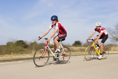 Active male athlete riding bicycles on an open country road Stock Photo - 13929352