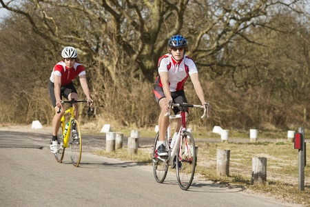 Active male athletes riding bicycles on a country road Stock Photo - 13929376