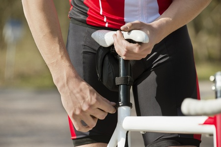 adjusting: Midsection of man adjusting the seat of his bicycle