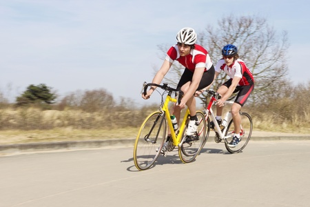 'cycles: Active male cyclists in sportswear riding cycles on an open country road