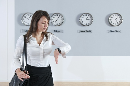 timezone: Young businesswoman checking time with world time zone clocks in background