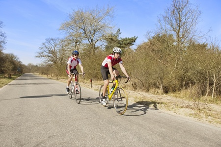 Two male cyclists riding bikes in a rural area on a sunny day Stock Photo - 13929377