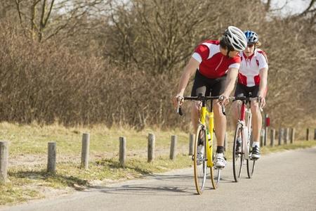 jinete: Dos atletas jóvenes en bicicleta en un camino rural