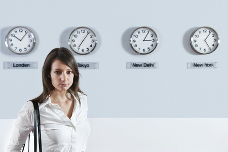 Portrait of young businesswoman standing with world time zone clocks in background photo