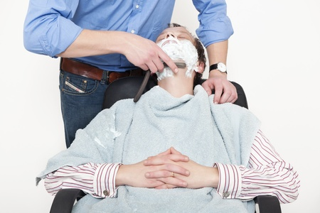 Man wrapped in towel being shaved with cut throat razor by barber over colored background photo