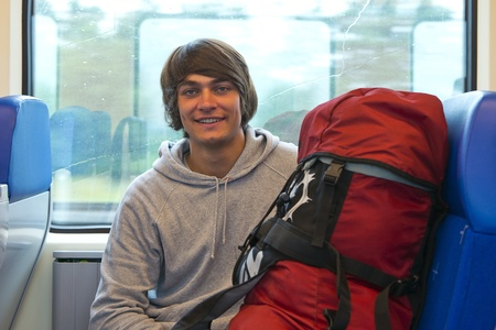 Backpacker smiling into the camera in front of a train window, with his back pack next to him photo