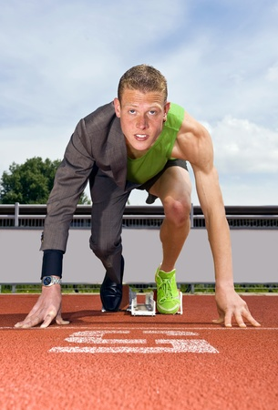 Conceptual image of an athlete (sprinter) ready to start a business career. Performane in business is top sport photo