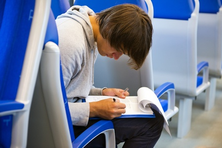 filling out: Young man, filling out his itinerary in a binder, sitting sideways in a train