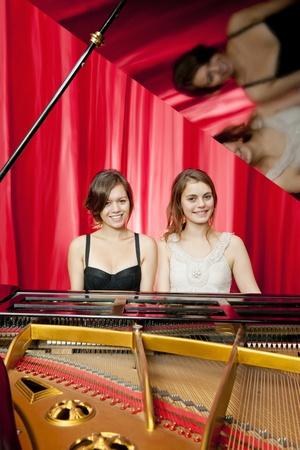 Pretty girls on a concert stage play two part harmony on a single grand piano photo