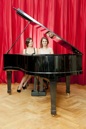 grand piano: Two pretty young women in formal dress harmonize on a single grand piano