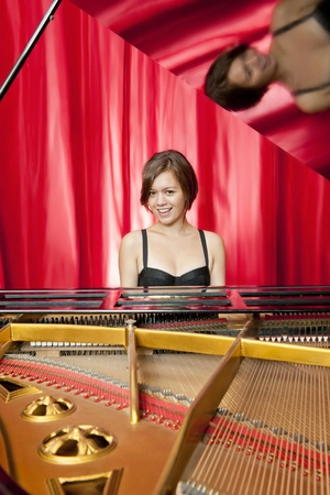 Formal concert on stage as a pretty young woman plays classical music on a grand piano photo