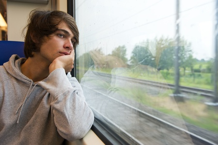passing: Bored young man, staring out the train window on a rainy, grey and dull day