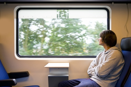 Young man looking out of the window of a train on a grey, rainy day photo