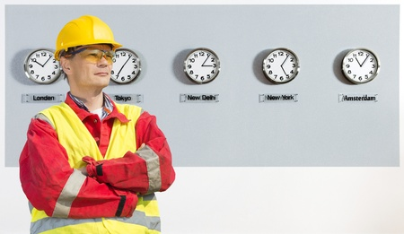 worker, wearing coveralls, safety goggles and a hard hat in front of a wall, with five clocks, displaying the time in various parts of the world photo