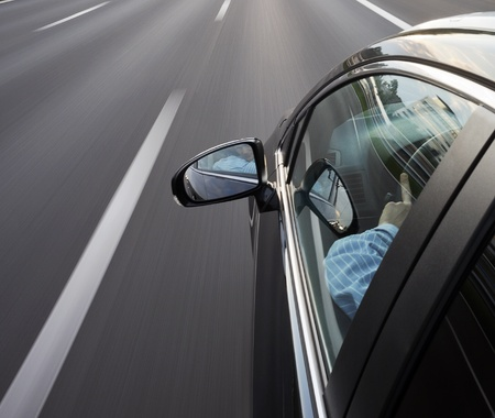 Car speeidng along the motorway, with the driver looking in his mirror photo