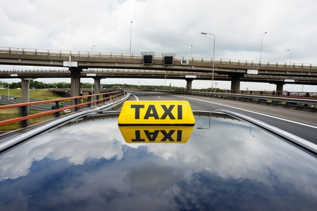 Cab driving over a flyover, with a taxi sign on the rooftop of the car photo