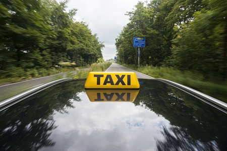 Taxi sign on tyop of a car, driving on a dual carriage way photo