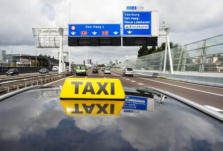 Taxi driving on a multiple lane motorway towards a big city photo