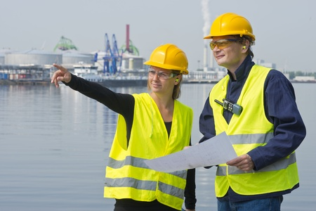 Female project engineers discussing a blueprint of a new construction site with her colleague in a harbor setting