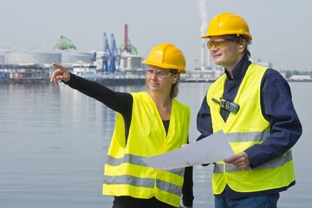 Weibliche Projektingenieure diskutieren eine Blaupause einer neuen Baustelle mit ihrer Kollegin in einem Hafen Einstellung Standard-Bild