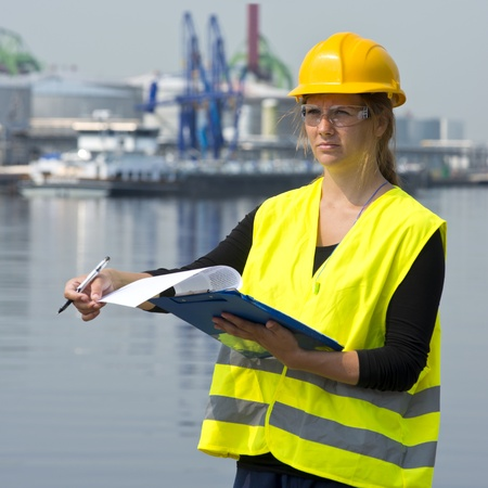 Female foreman turning a page on her clip board during her inspection rounds through an industrial harbor photo