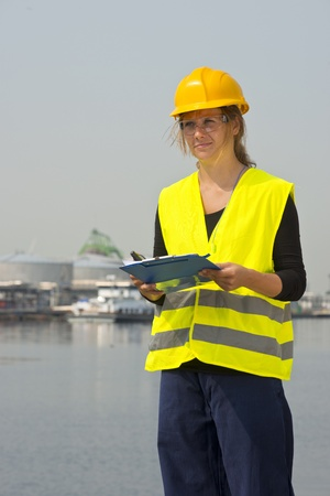 docker: Feamale engineer with hard hat, safety goggles and a safety vest in a harbor district