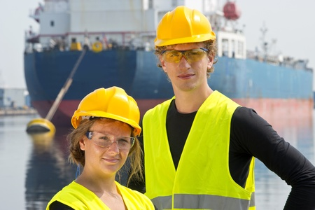 entrepreneurial: Male and female entrepreneurial engineers posing happily in front of a large industrial vessel