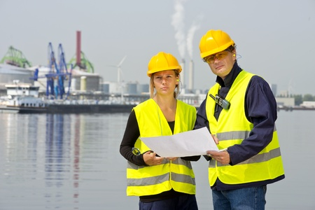 Two harbor workers discussing plans and blueprints for a new construction site on location at an industrial harbor photo