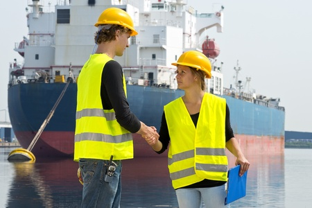 Female docker shakes hands with a male colleague in front of a large industrial cargo ship photo