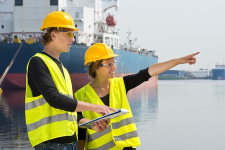 entrepreneurial: Two industrial engineers in a harbor, checking a plan from a clipboard on location Stock Photo