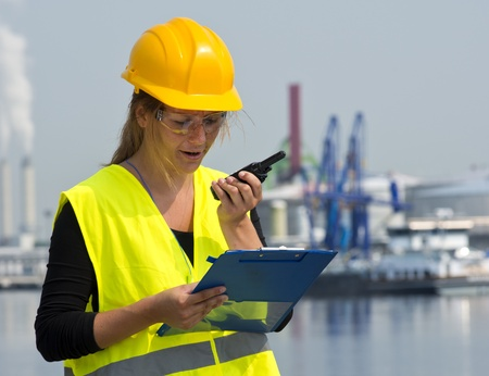 Woman, wearing a hard hat and safety goggles, and discussing business over a cb radio, whilst looking at notes on her clip board in an industrial harbor