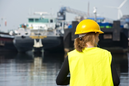 docker: Female docker overlooking a habor with moored supply vessels