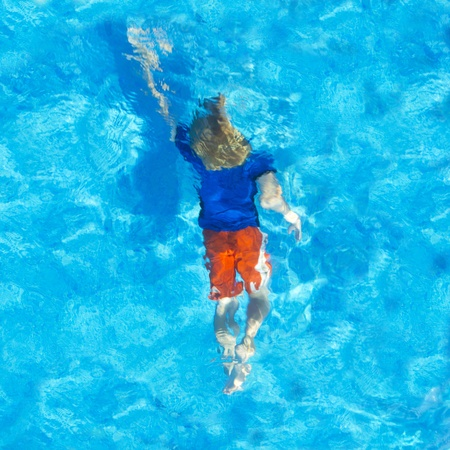 Young child swiming with his clothes on under water, seen from above photo