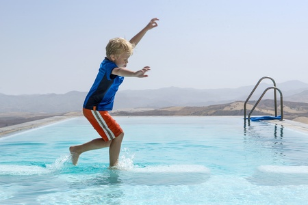 Young boy trying to keep his balance whilst jumping from one block to another in an infinity pool photo