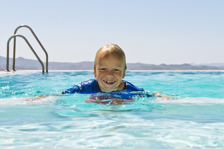 young child, chainging his milk teeth, swimming with his clothes on, and having fun in an infinity pool photo
