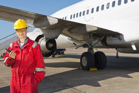 mantenimiento: Aviones ingeniero de pie con radio CB en frente de un avi�n comercial