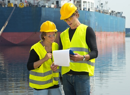 Two dockers checking the freight papers of a cargo vessel moored off in the background in a harbor