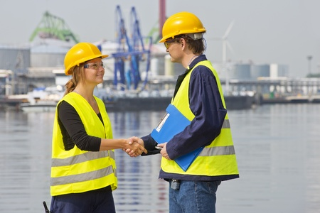 Two dockers greeting eachother in an industrial harbor, wearing the necessary safety gear photo