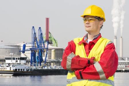 masculin: Engineer, wearing safety gear standing with his arms crossed and a confident, proud look on his face in front of an industrial harbor Stock Photo