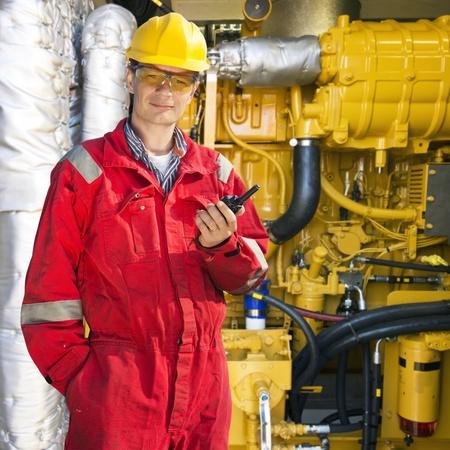 엔지니어, 입고 바지, 하드 모자와 안전 고글, 그의 HND 무선 통신 장치를 hoding, 거대한 유압 엔진의 앞에 포즈
