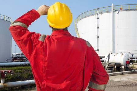 roughneck: Oil engineer looking at overdue maintenance and safety issues of storage tanks with crude oil supply