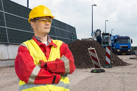 widening: Road construction worker, wearing an overall, safety vest and other safety precautions, overlooking the building site, with a dump truck and digger in the background, behind a pile of gravel and road markings
