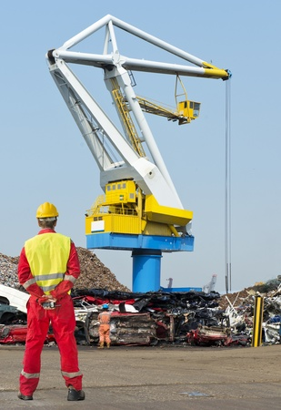 Engineer, wearing overalls, safety shoes, a reflective vest and hard hat, standing with his hands behind his back, holding a CB readio, looking out at a huge heavy duty harbor crane and the car graveyard photo