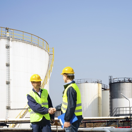 petrochemistry: Two oil industry workers shaking hands in front of the storage tanks of a petrochemical refinary