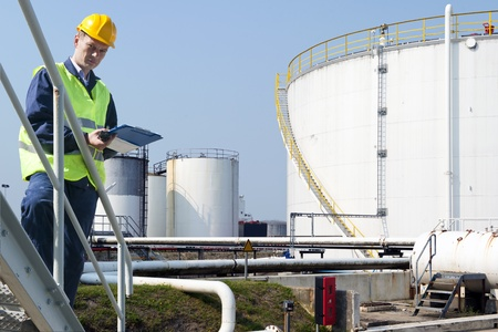 audit: Engineer with a clipboard taking notes of the quality and state of oil silos of a petrochemical industry for safety reasons