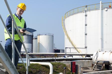 control de calidad: Ingeniero con un portapapeles tomando notas de la calidad y el estado de los silos del petróleo de una industria petroquímica por razones de seguridad