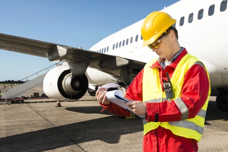 Aircraft engineer with a checklist of several pages on a clipboard Stock Photo - 15045024