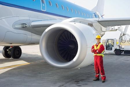 고치다: 활주로 옆 상업용 항공기에 포즈 제트 엔진 정비사
